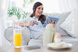 Laughing brunette buying online while having breakfast