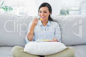 Cute woman sitting on the couch crossing legs eating fruits