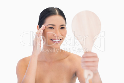 Natural dark haired model holding mirror touching her temple