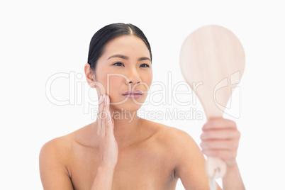 Natural dark haired model holding mirror touching her cheek