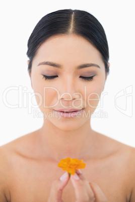 Natural black haired model holding orange flower