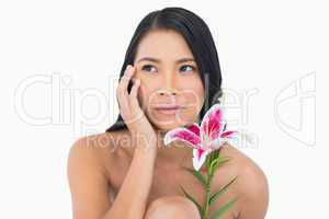 Natural model posing with lily and touching her face