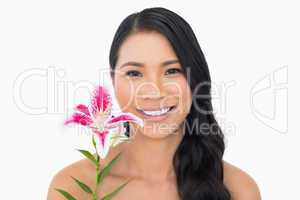 Smiling natural brown haired model holding lily