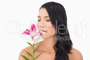 Natural brown haired model smelling lily closing eyes