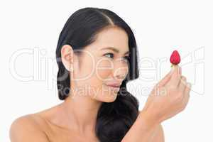 Gorgeous brown haired model holding strawberry