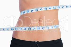 Fit belly surrounded by measuring tape