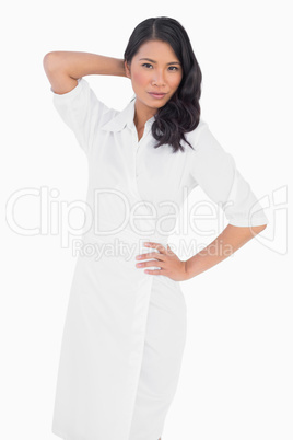 Elegant dark haired model with white dress posing
