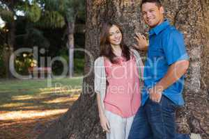 Couple leaning on a tree