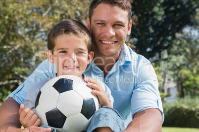 Happy dad and son with a football in a park
