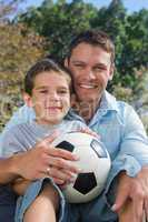 Cheerful dad and son with football