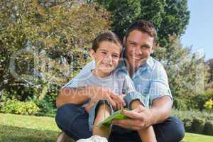 Smiling dad and son holding a leaf