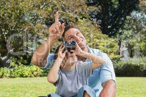 Dad and son looking at the sky with binoculars