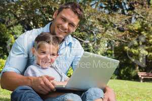 Smiling son and dad with a laptop