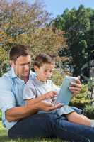 Dad and son playing with a tablet pc in a park
