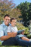 Dad and son with tablet pc smiling into the camera