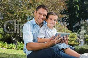 Happy dad and son with a tablet pc
