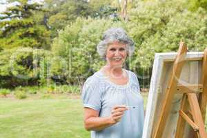 Smiling retired woman painting on canvas