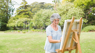 Peaceful retired woman painting on canvas