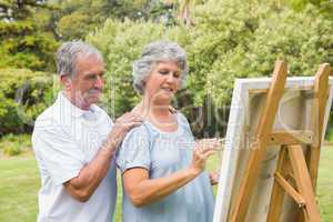 Peaceful retired woman painting on canvas with husband