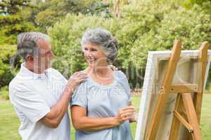 Happy retired woman painting on canvas with husband