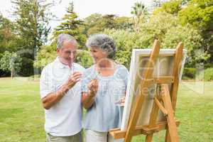 Smiling retired woman painting on canvas with husband