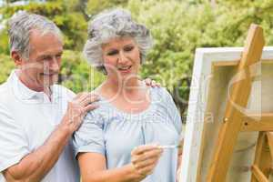 Happy retired woman painting on canvas and talking with husband