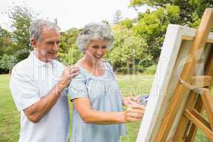 Content retired woman painting on canvas and talking with husban