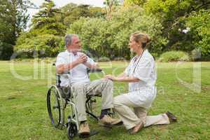 Smiling man in a wheelchair talking with his nurse kneeling besi