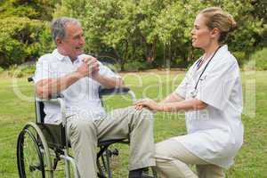 Cheerful man in a wheelchair talking with his nurse kneeling bes