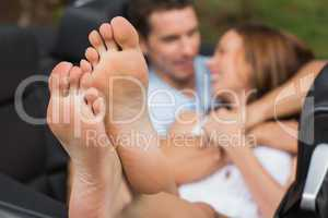 Cute couple cuddling in the backseat with focus on foot