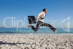 Cheerful businessman jumping on the beach