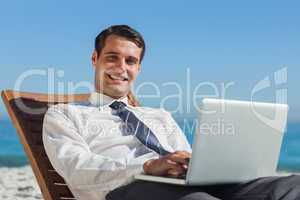Cheerful young businessman lying on a deck chair with his comput