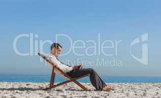 Young businessman resting on his deck chair using his tablet