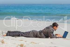 Young businessman lying on the sand typing on his laptop