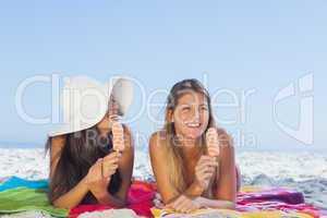Smiling pretty women lying on their beach towel