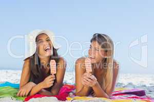 Cheerful pretty women lying on their towel eating ice cream