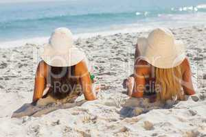Attractive blonde and brunette in bikinis lying on the sand