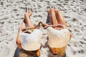 Sexy blonde and brunette wearing straw hat clinking their glass
