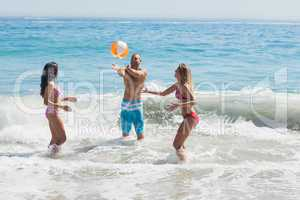 Cheerful friends playing with a beachball in the sea