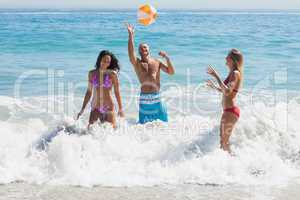Happy friends playing with a beachball in the sea