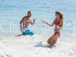 Cheerful friends throwing water to each other in the sea