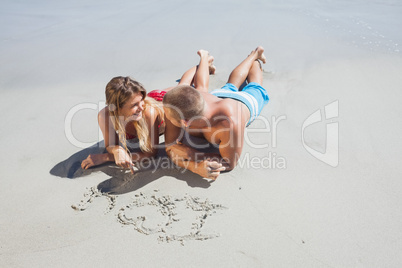 Loving couple drawing in the sand