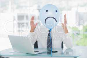 Blue balloon with sad face hiding angry businessmans face