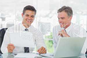 Smiling businessman listening to his intern while explaining doc