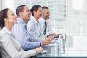 Coworkers smiling while listening to presentation