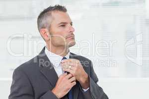 Serious businessman tightening up his tie