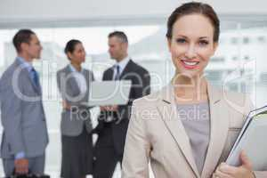Cheerful businesswoman holding files smiling at camera