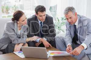 Business people analyzing financial graphs of their company