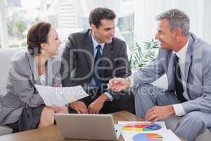 Cheerful business people analyzing financial graphs of their com