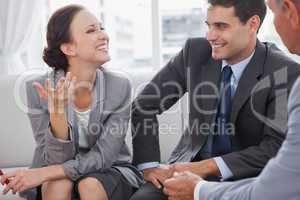 Businesswoman smiling while her partners looking at her